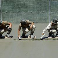 Trys vyrai betonuoja grindis.